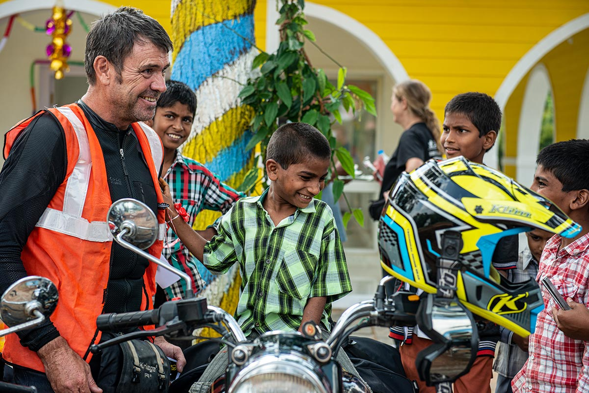 Alex Pirie with Indian children on motorcycle adventure