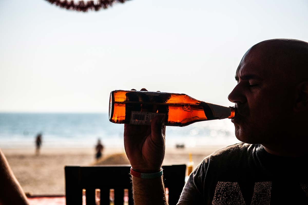 man drinking a beer on the beach
